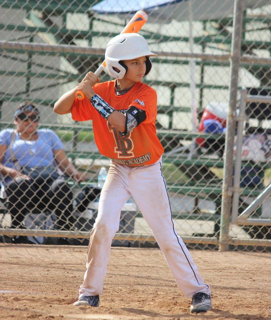 youth baseball player at bat wearing white pants orange jersey and white helmet