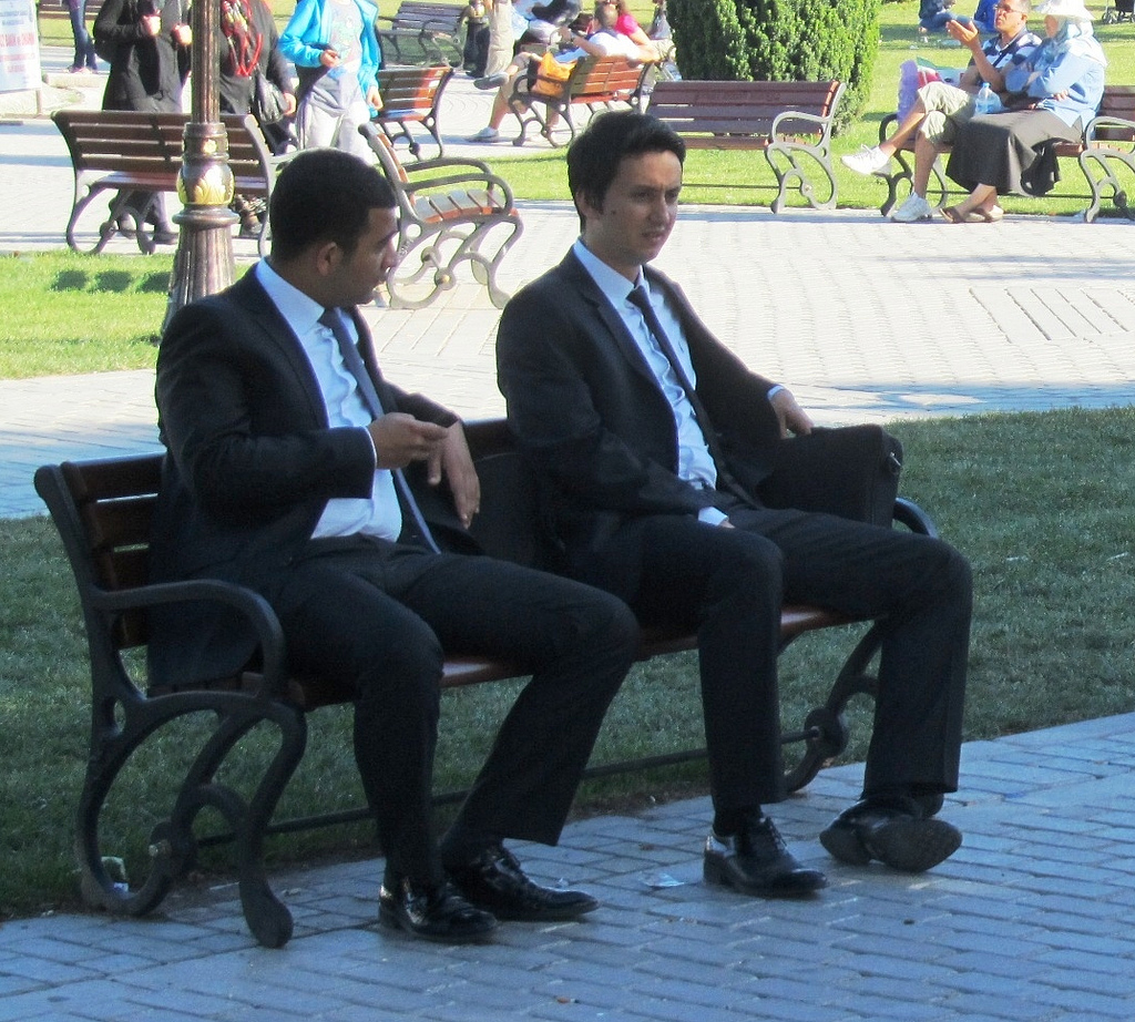men in suits sitting on bench
