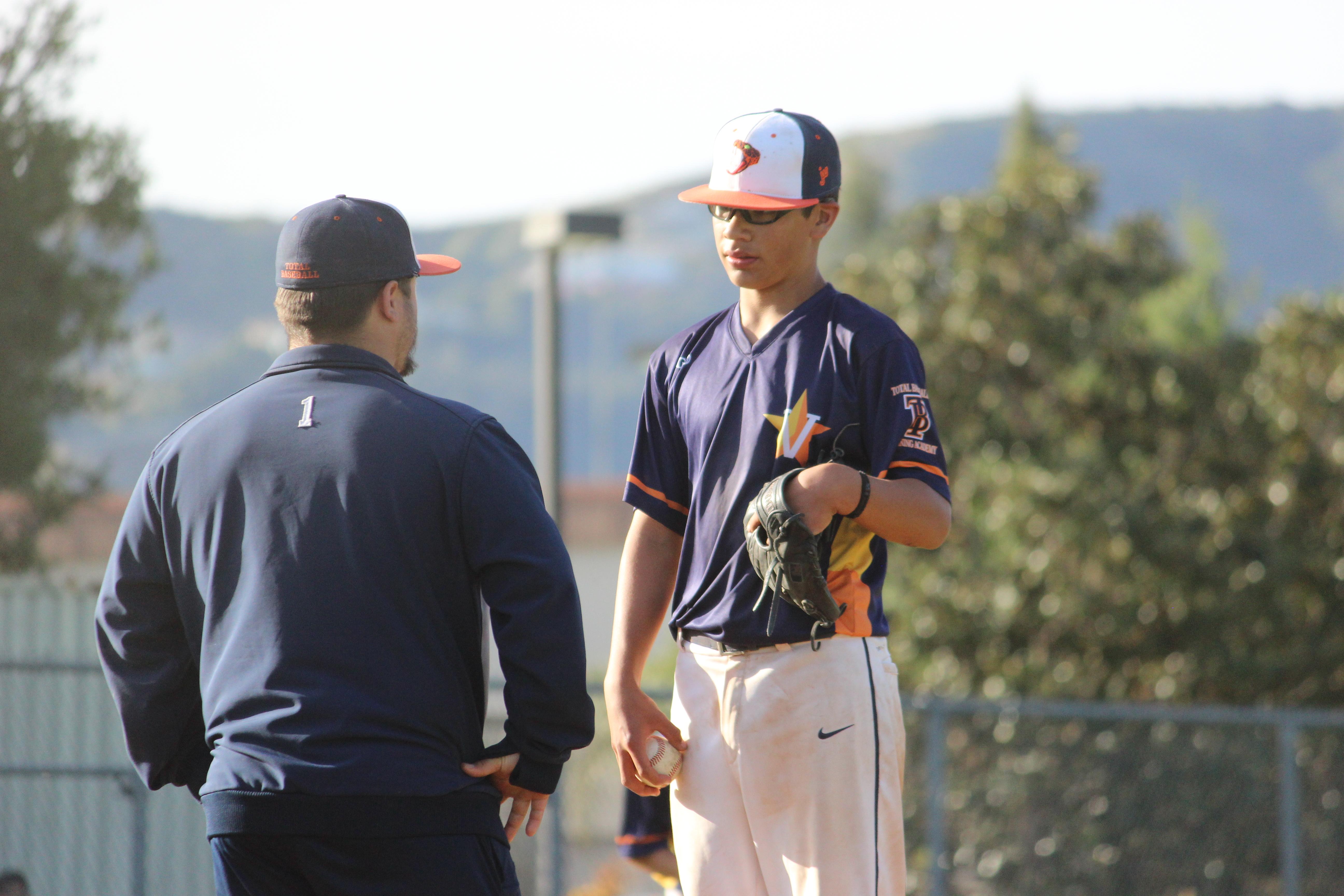 coach and taller baseball player