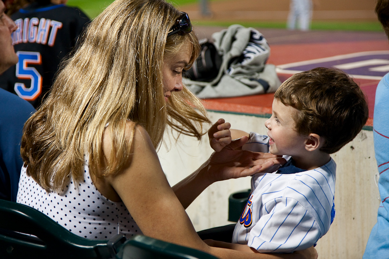 mom helping young baseball player