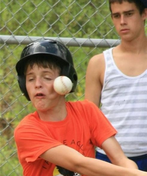 boy getting hit in the face with baseball