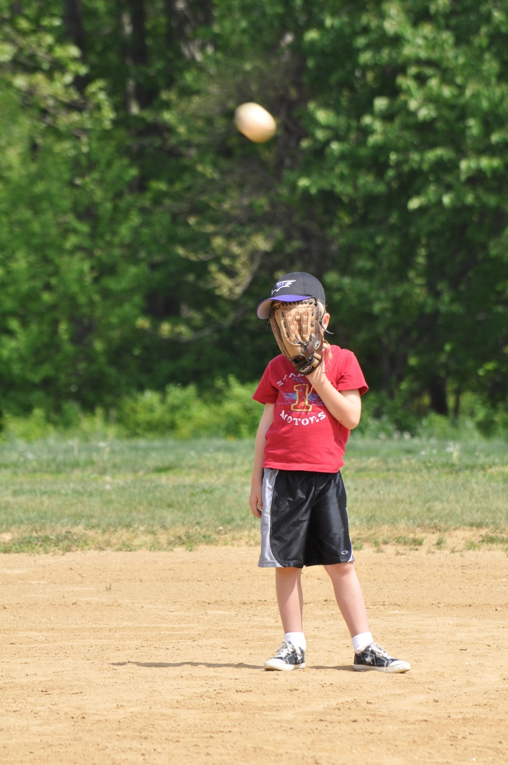 boy covering his face for a fly ball
