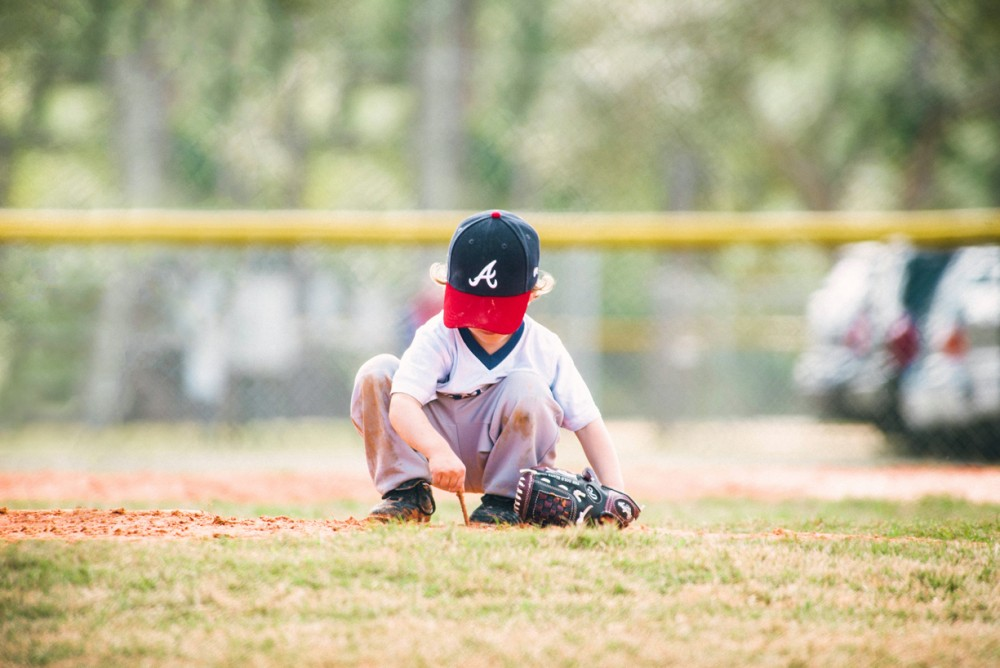 kid playing with grass during game