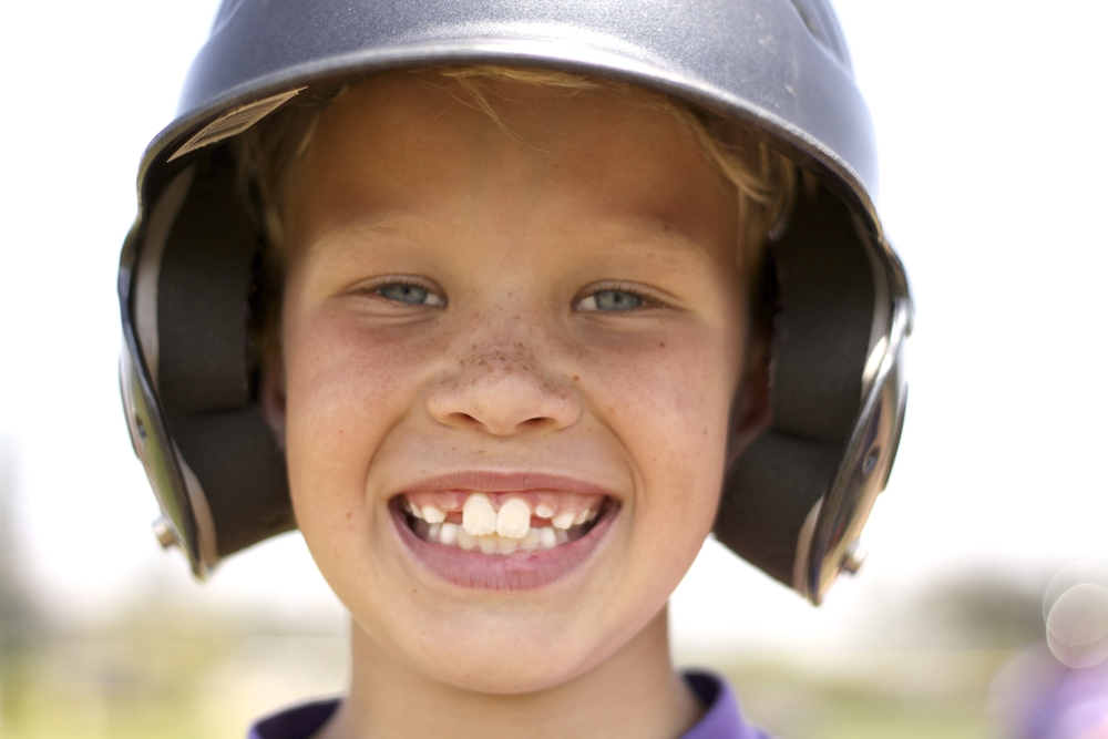 smiling boy in baseball helmet