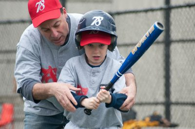 coach helping with bat grip
