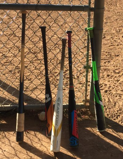 baseball bats against fence